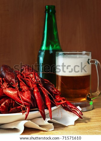 red boiled crawfishes and mug of beer - stock photo