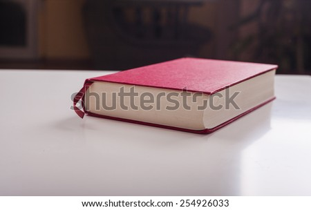 Red book on white table - stock photo