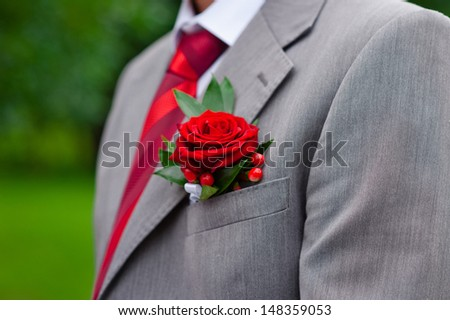 Red boutonniere on gray groom's jacket - stock photo