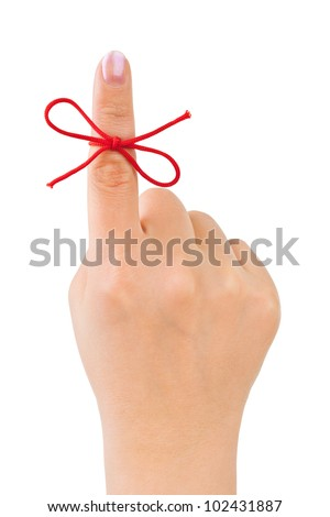 Red bow on finger isolated on white background - stock photo