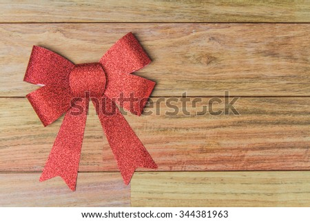 Red bow ribbon on wood background - stock photo