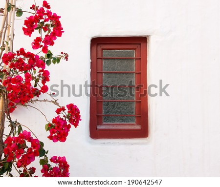 Red box on a white building with beautiful bougainvillea flowers - stock photo