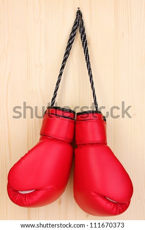 Red boxing gloves hanging on wooden background - stock photo