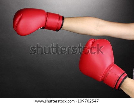 Red boxing gloves on hands on grey background - stock photo