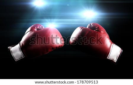 Red boxing gloves with the glow of flashes in the background. - stock photo