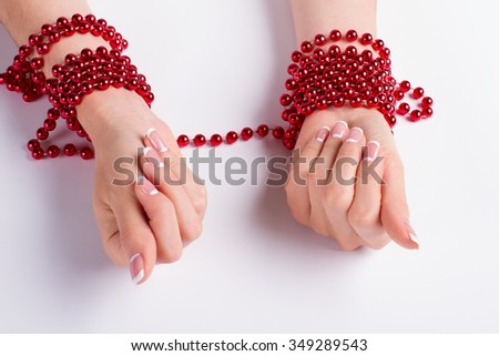 Red bracelets with beads on the female hands. Beautiful french manicure. Beauty saloon. - stock photo