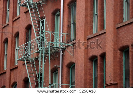 red brick building with green fire escape - stock photo