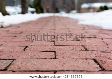 Red brick footpath from low angle close up in a snow day - stock photo