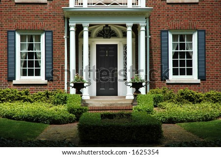 Red brick house with black shutters and green shrubs with front door flanked by pillars and two flower iron urns; luxury home / house - stock photo