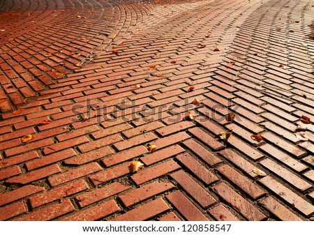 Red brick road split into two directions with herringbone pattern requiring a decision - stock photo