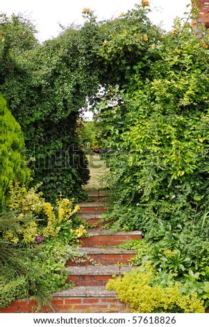 Red Brick Steps leading under an archway into an English garden - stock photo