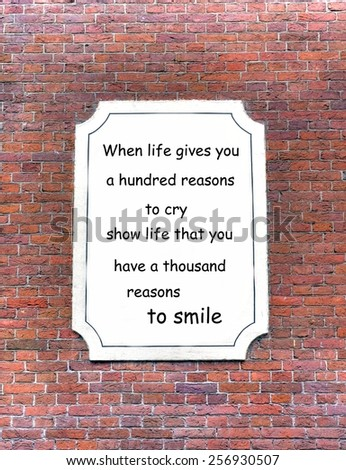 red brick wall background with a white board attached. On the board a quote about  life - stock photo