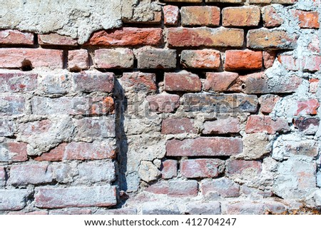 red brick wall with damaged, weathered plaster, texture - stock photo