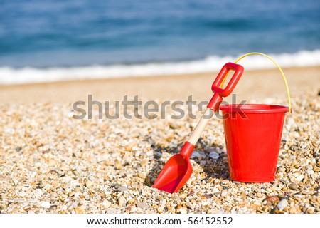 Red Bucket And Spade Lying On A Beach - stock photo
