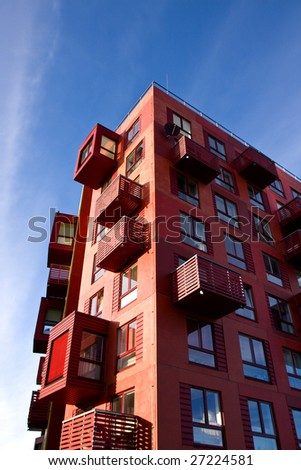 Red building with balconies and blue sky. Vertical. More buildings in my portfolio. - stock photo