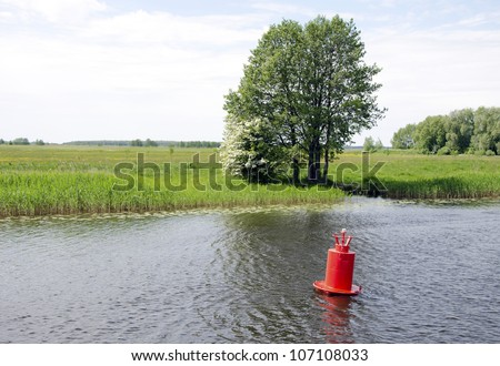 Red buoy beacon in lake shore water mark of ships swimming area. Meadow fields near lake. - stock photo