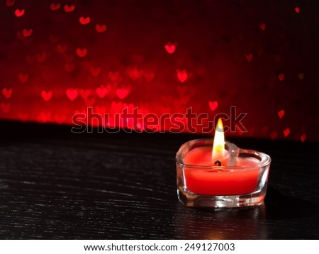 red burning heart shaped candle on red hearts bokeh background, valentine day and love concept - stock photo