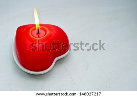 Red burning heart shaped candles over white background. Valentine - stock photo