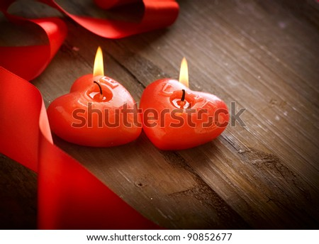 Red burning heart shaped candles over wood background. Valentine - stock photo