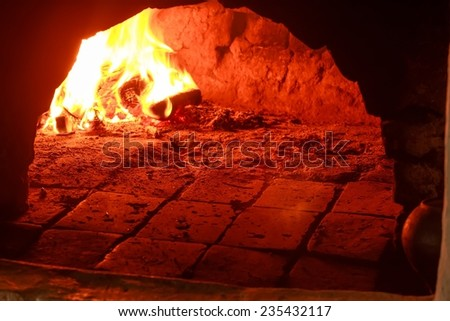 Red burning wood in a traditional hearth furnace - stock photo