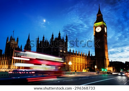 Red bus in motion, Big Ben and Westminster Palace in London, the UK. at night. View from Westminster Bridge. Moon shining on dark blue sky - stock photo