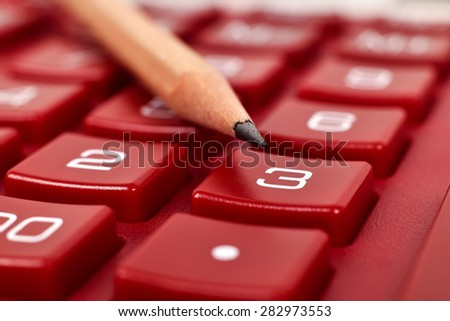 red calculator with pencil, extra close up - stock photo