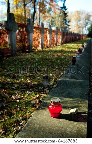 Red candle on cementery during Halloween holiday - stock photo