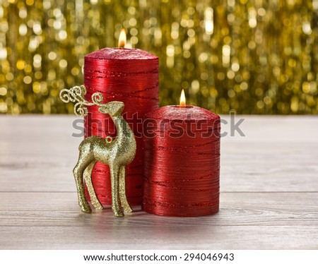 Red candles and Reindeer in front of a golden background - stock photo