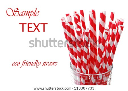Red 'candy striped' environmentally friendly straws (biodegradable paper printed with soy-based ink) on white background with copy space.  Macro with shallow dof. - stock photo