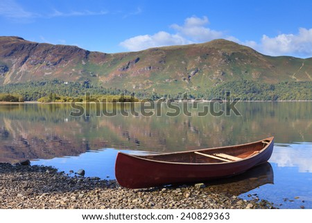 Red Canoe. A red canoe on the banks of Derwentwater.  In the background is Catbells a fell in the English Lake District National Park. - stock photo