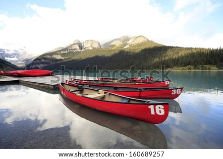 Red canoes reflected in Lake Louise, Banff Provincial Park  - stock photo