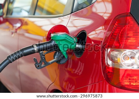 Red car at gas station being filled with fuel - stock photo