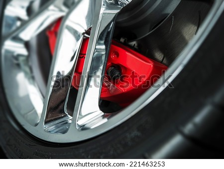 Red Car Brakes Closeup and Chromed Alloy Wheel. Low Profile Sport Tire - stock photo