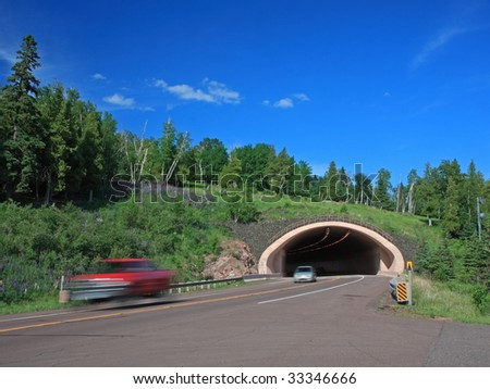 red car moving out of tunnel, lake Superior north shore - stock photo
