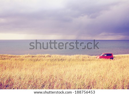 Red car parking in the field with retro filter effect  - stock photo