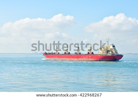 Red cargo ship (bulk carrier) sailing by the coast of Vlissingen, the Netherlands - stock photo