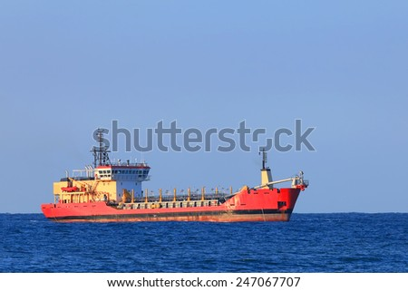 Red cargo ship in a distance in the sea - stock photo