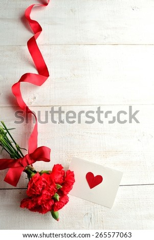 Red carnations bouquet with heart message card - stock photo