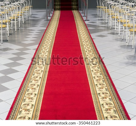 Red carpet leading to the stage in an empty auditorium. - stock photo