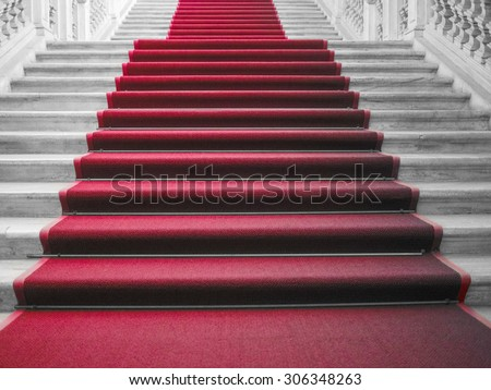 Red carpet on a stairway used to mark the route taken by heads of state, vips and celebrities on ceremonial and formal occasions or events - stock photo