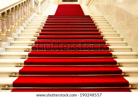 Red carpet on the stairs in a luxury interior - stock photo