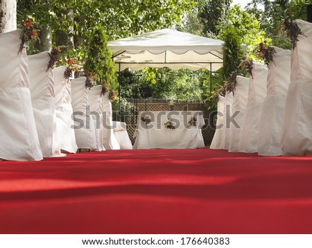 Red carpet patch to altar for outdoor wonderful wedding - stock photo