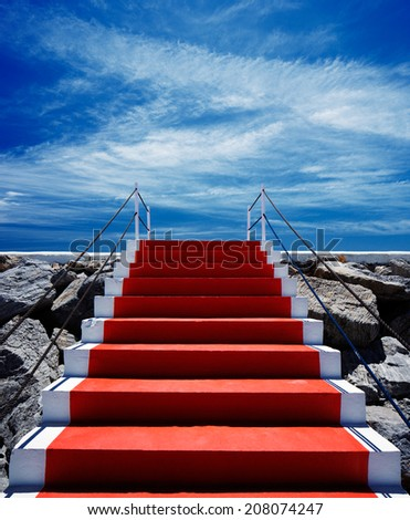 Red carpet stairway leading to heaven with stanchions barriers on both sides - stock photo