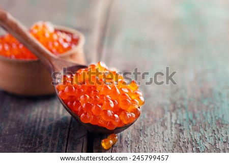 Red caviar in spoon on aged wooden background.  Selective focus. - stock photo