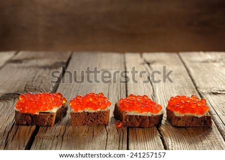 Red caviar on rye bread and butter on wooden background - stock photo