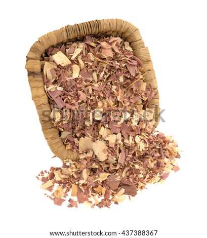 Red cedar shavings used for pet bedding spilling from an old wicker basket isolated on a white background. - stock photo