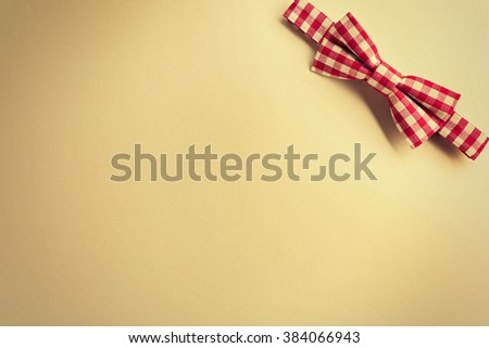 Red cell bow tie on beige background - stock photo