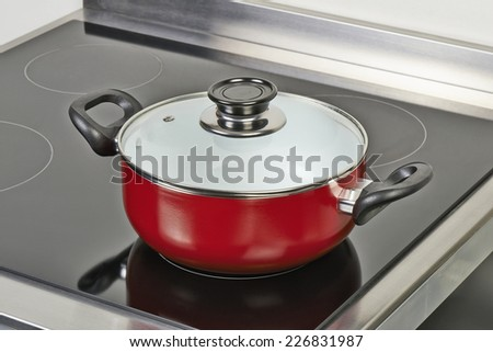 Red ceramic pan with cover on Electric hob in modern and domestic kitchen, view from above - stock photo