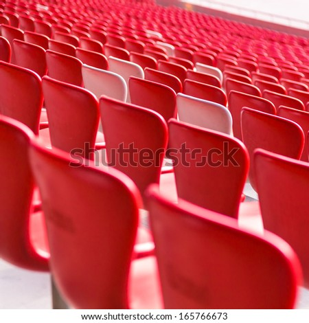 Red chairs bleachers in large stadium - stock photo