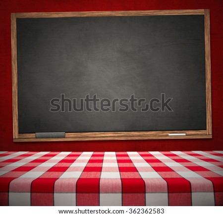 Red checkered dining table on black chalkboard hanging on red wall - stock photo
